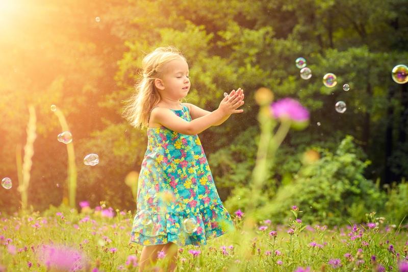 blondes Mädchen hat Spaß beim Spielen mit Seifenblasen