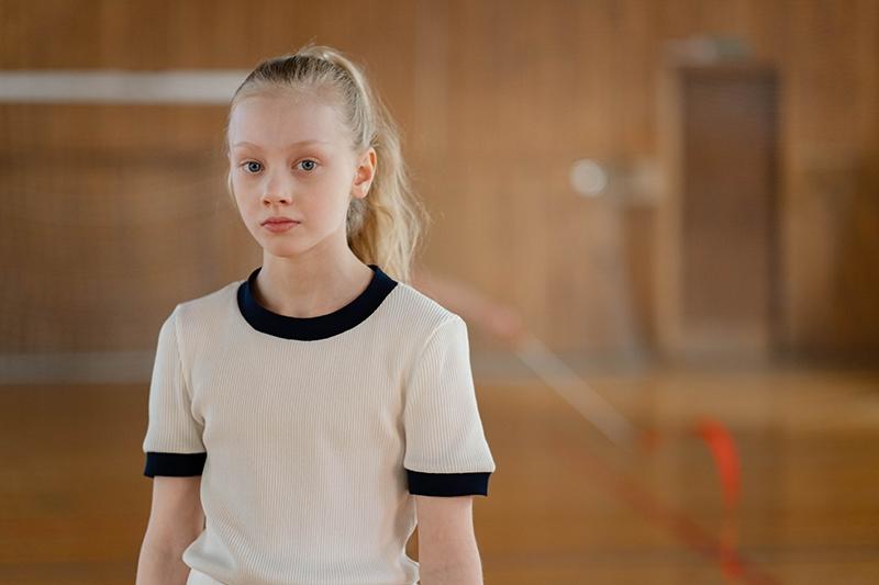blondes Mädchen im weißen T-Shirt, das im Fitnessstudio steht