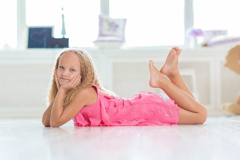 Blondes kleines Mädchen im rosa Kleid auf dem Boden im Zimmer liegend