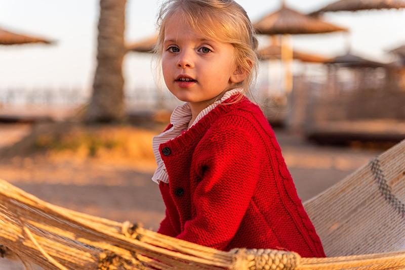 Blondes kleines Mädchen im roten Pullover sitzt am Strand