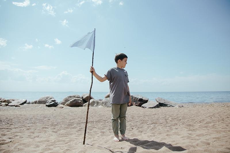 der Junge, der einen Stock hält, während er am Strand steht