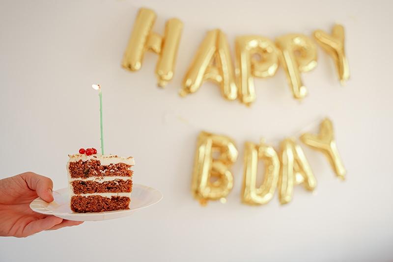 die Person, die ein Stück Kuchen mit einer Kerze hält