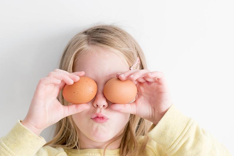 ein Mädchen, das zwei Eier hält und damit die Augen bedeckt
