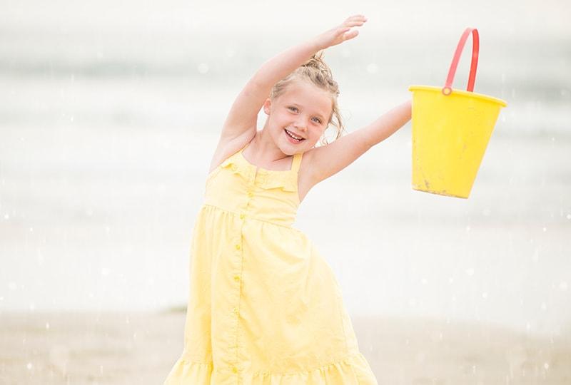 ein Mädchen im gelben Kleid mit einem Plastikeimer am Strand