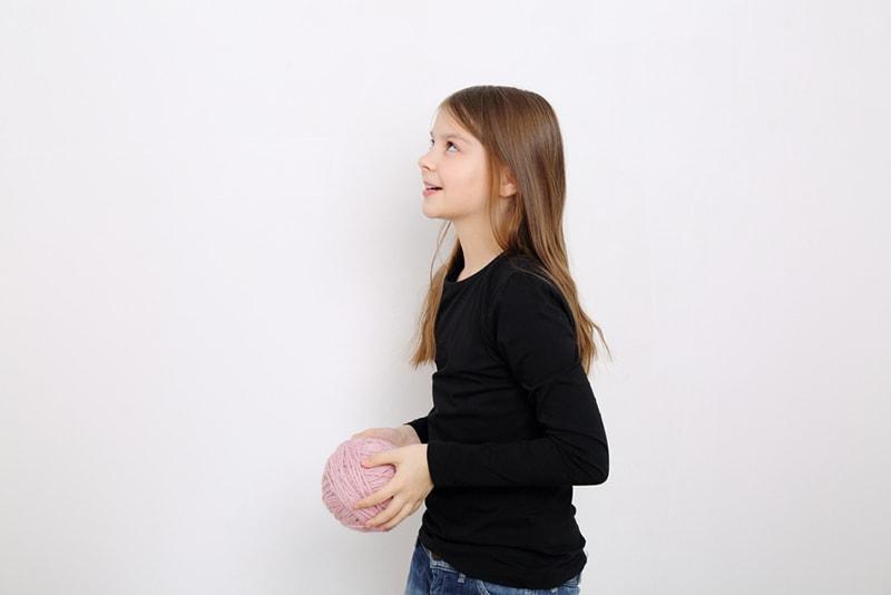 ein Mädchen, das einen Wollknäuel hält und aufschaut