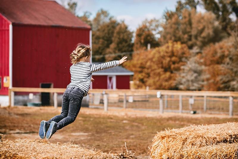 kleines Mädchen springt auf Heuballen auf Bauernhöfen