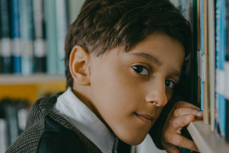 ein kleiner Junge, der sich mit Büchern an Regale lehnt