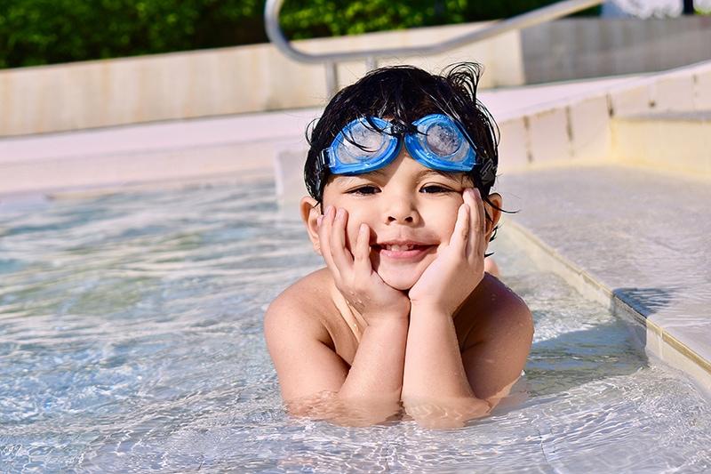 ein kleiner Junge in einem Schwimmbad, der sich auf seine Hände stützt