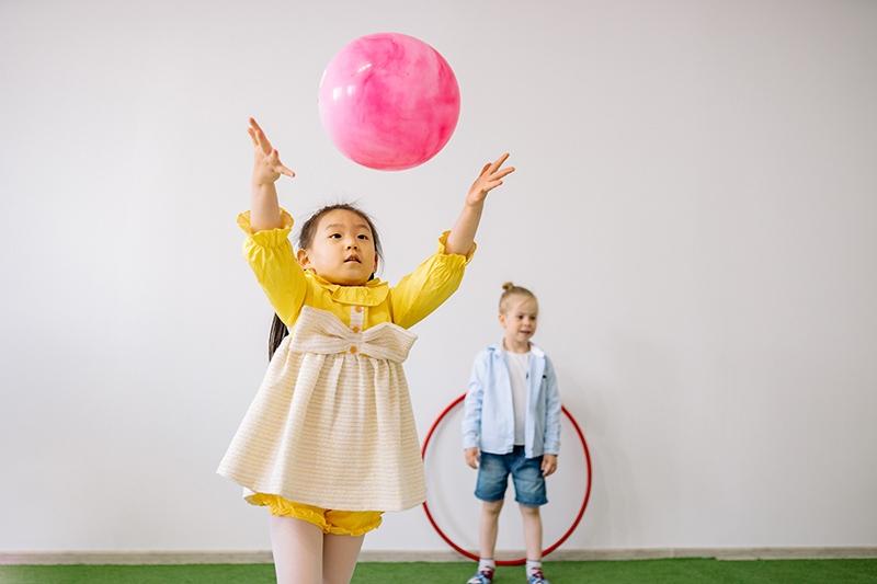 ein kleines Mädchen, das einen Ball ins Zimmer wirft