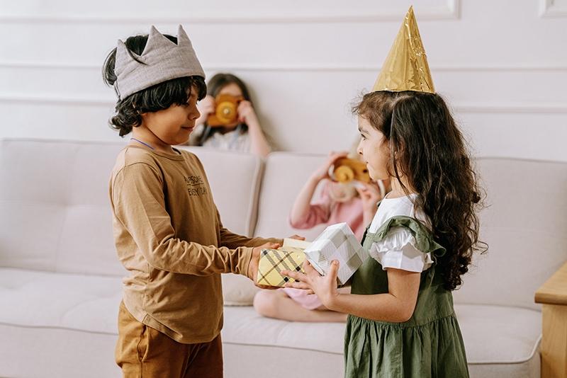 ein kleines Mädchen und ein Junge, die Geschenke auf der Geburtstagsfeier austauschen