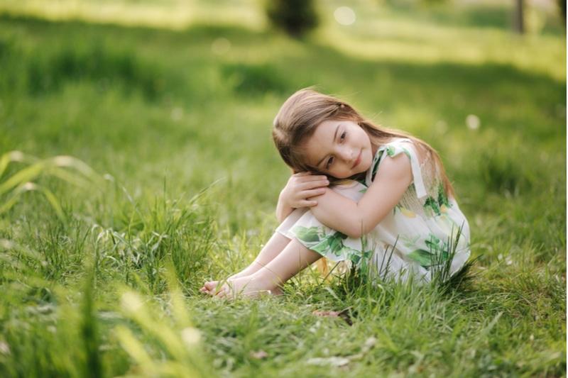 entzückendes kleines Mädchen sitzt barfuß auf dem Gras im Park