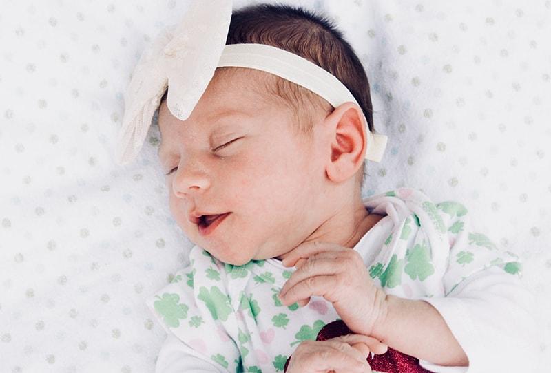entzückendes Baby, das auf dem Bett schläft und sich streckt