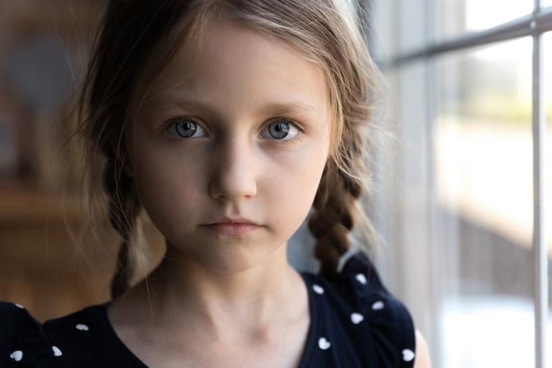 ernstes trauriges kleines Mädchen schaut in die Kamera