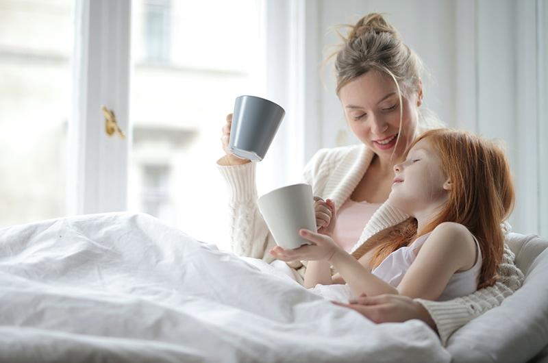 fröhliche Frau, die mit Tochter spricht, während sie Tee in einem Bett trinkt