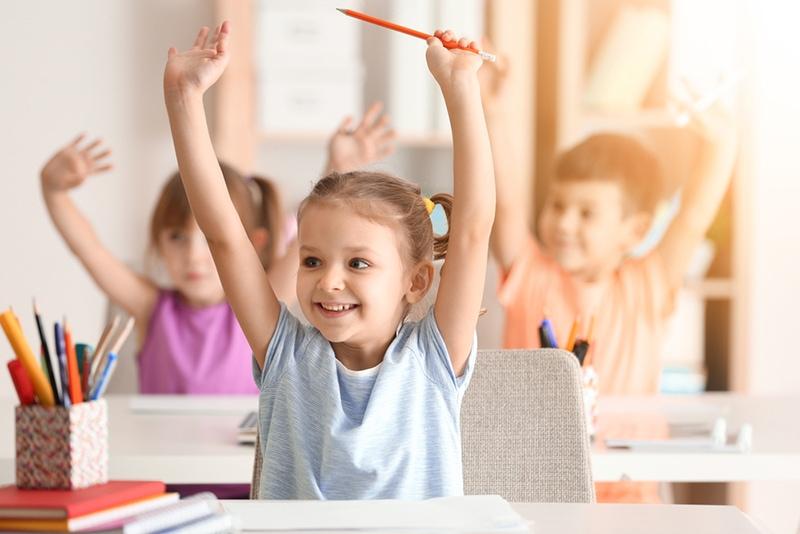 fröhliche Kinder, die im Klassenzimmer die Hände heben