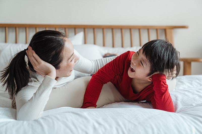 fröhliche Mutter und Sohn reden auf dem Bett