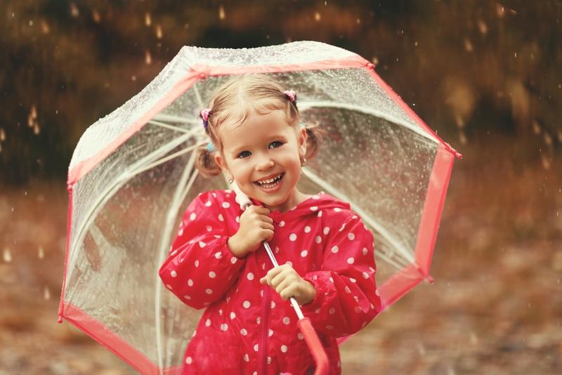 glückliches Kindermädchen, das mit einem Regenschirm im Regen lacht