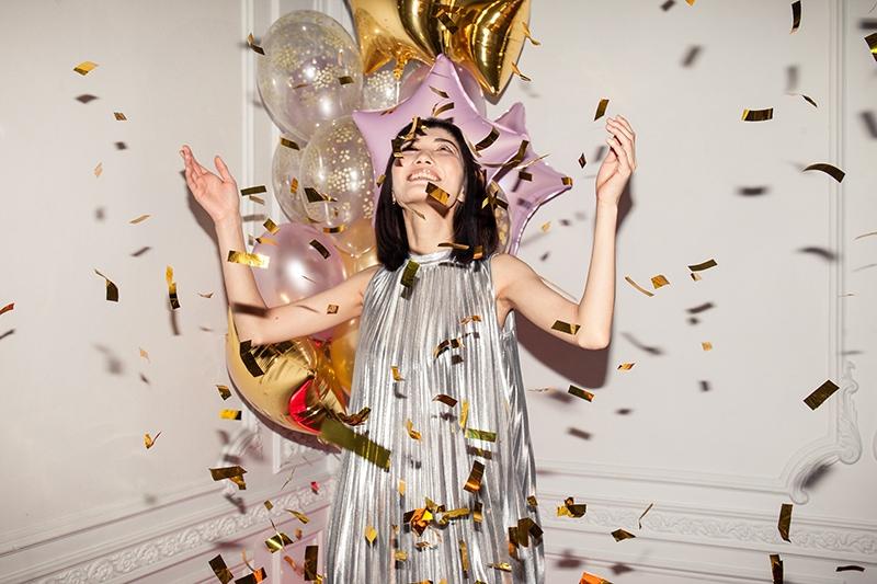 glückliche Frau, die auf der Party fallendes Konfetti betrachtet