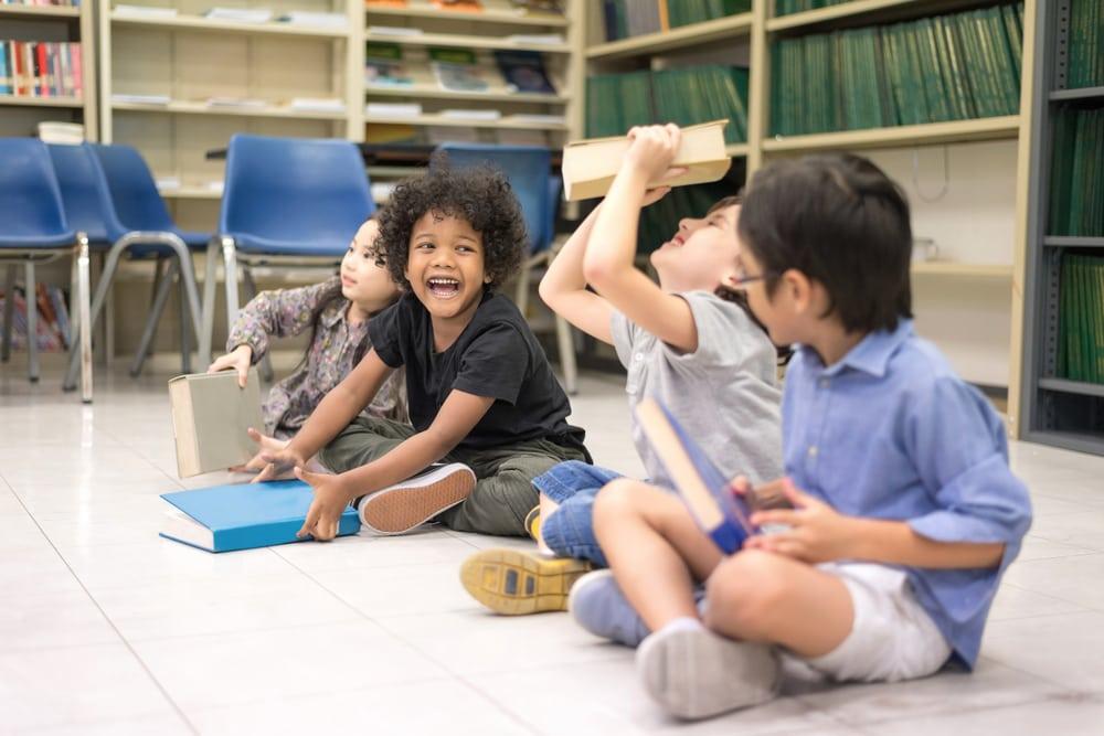 glückliche Kinder, die mit Büchern spielen, die im Klassenzimmer auf dem Boden sitzen