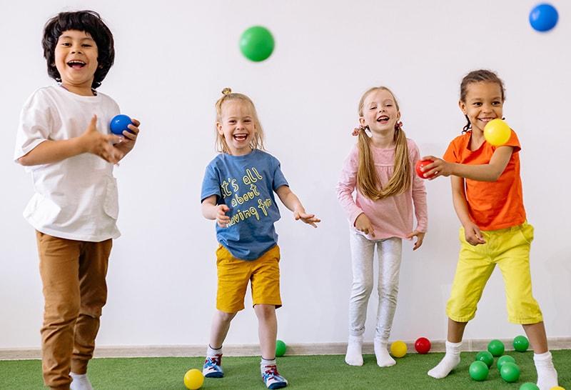 glückliche Kinder spielen mit bunten Plastikbällen im Zimmer