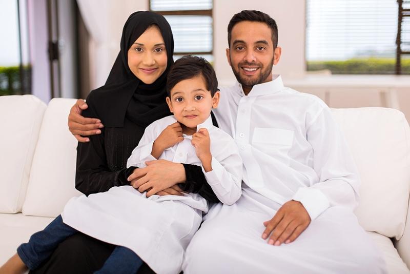 glückliche muslimische Familie, die zu Hause auf der Couch sitzt
