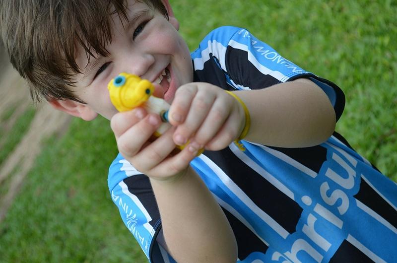 glücklicher Junge, der Wasserpistole hält, während er auf dem Gras steht