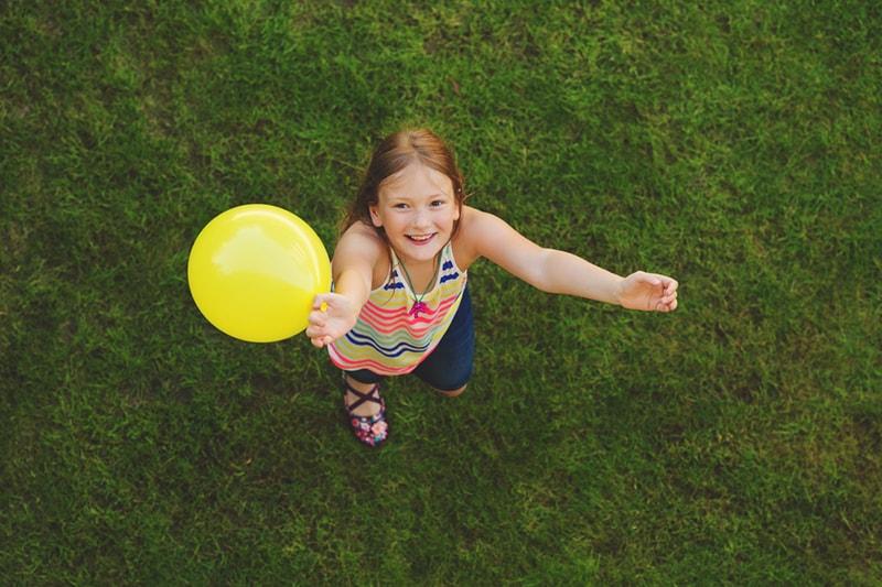 glückliches Mädchen, das einen gelben Ballon hält, der auf dem Gras steht