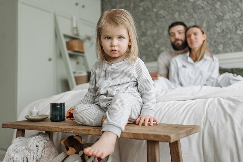 kleine Mädchen sitzen auf der Bank vor den Eltern, die hinter ihr auf dem Bett sitzen
