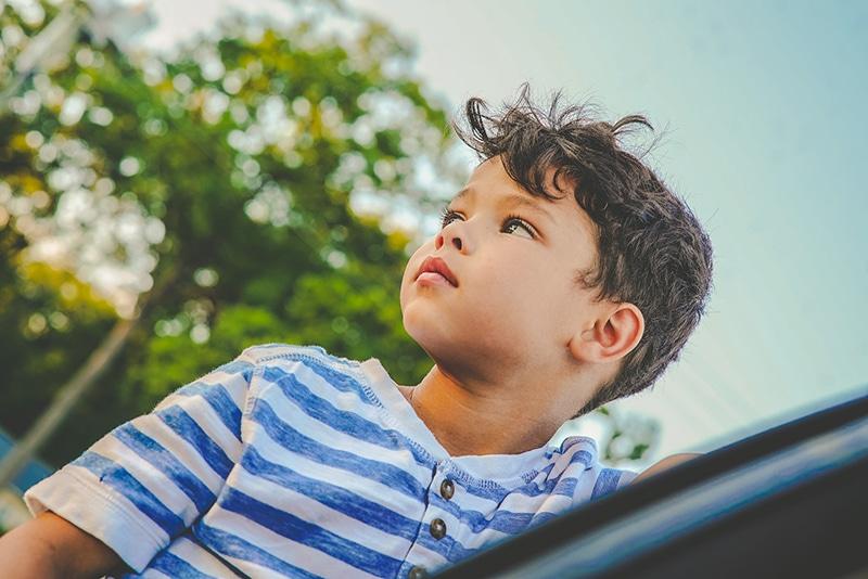 kleiner Junge, der draußen steht und beiseite schaut