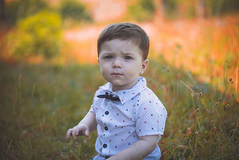 kleiner Junge mit Hemd sitzt auf der Wiese