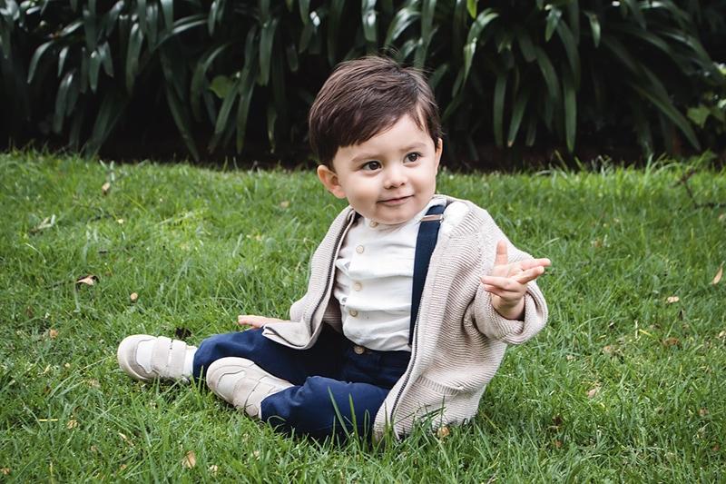 kleiner Junge sitzt auf dem Gras im Park