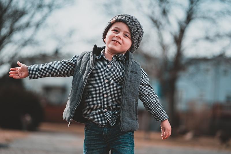 kleiner Junge steht auf der Straße und breitet die Arme aus
