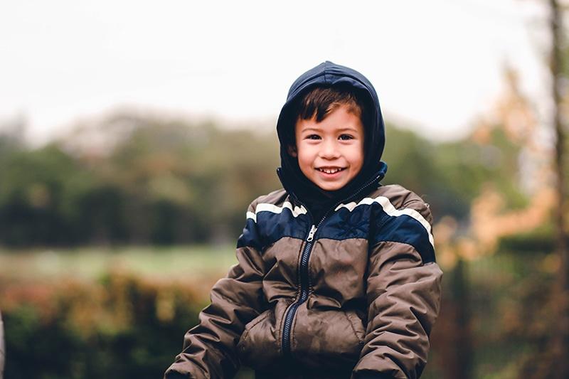 kleiner lächelnder Junge in der Jacke, der im Freien steht