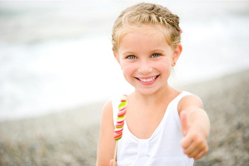 kleines Mädchen mit einer Süßigkeit auf Zeigen Sie den Daumen
