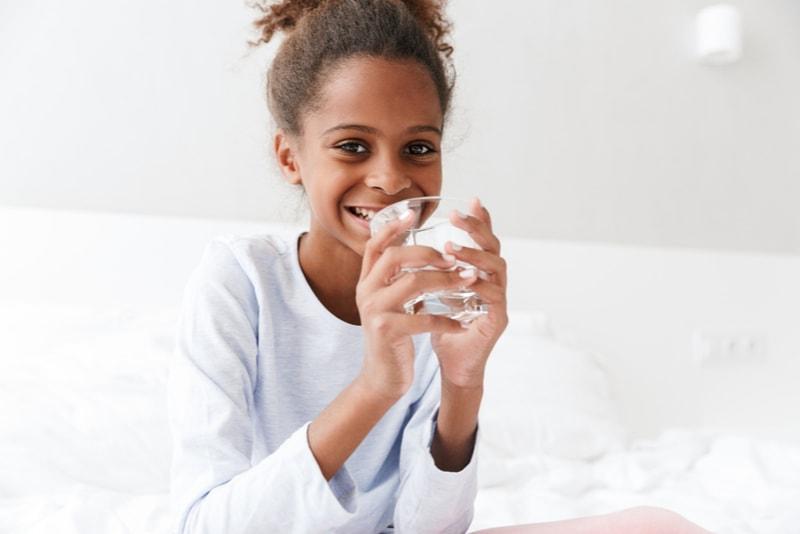 kleines Mädchen trinkt Wasser aus Glas