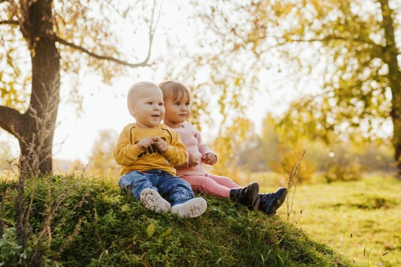 kleines Mädchen und Kleinkind sitzen auf dem Gras
