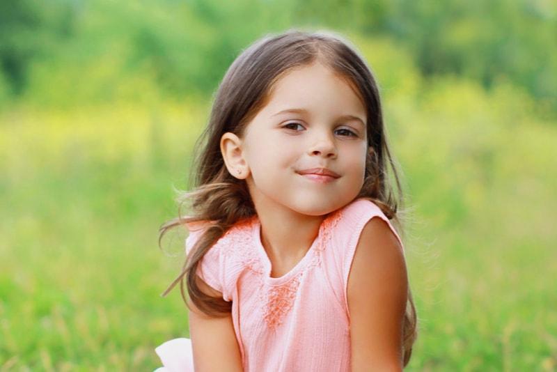 kleines Mädchenkind auf dem Gras am sonnigen Sommertag