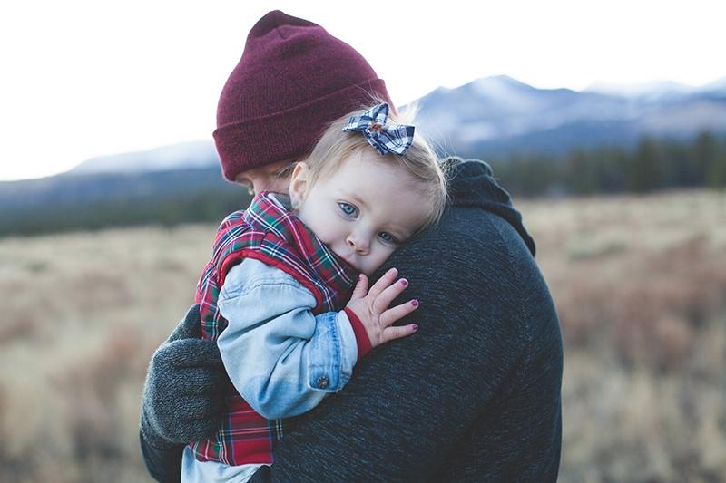 kleines Mädchen, das sich auf die Schulter ihres Vaters stützt, während er sie in den Armen hält