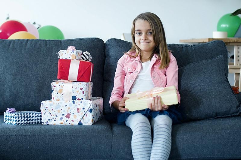 kleines Mädchen mit Geburtstagsgeschenk auf der Couch sitzend