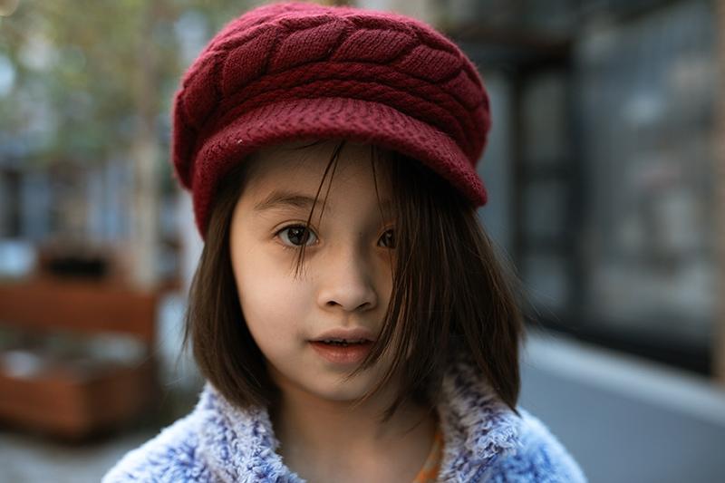 kleines Mädchen mit kurzen Haaren mit roter Mütze