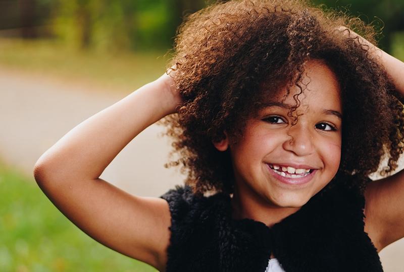 kleines Mädchen mit lockigem Haar, das lächelt, während es das Haar mit den Händen berührt
