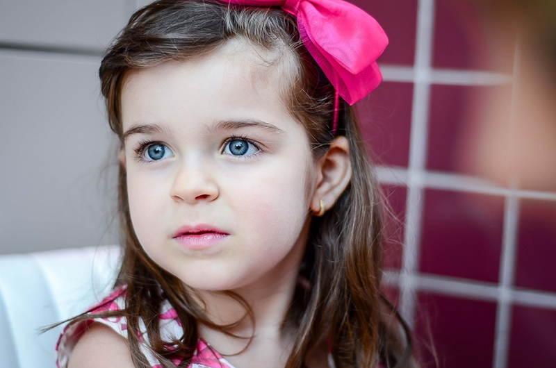 kleines Mädchen mit rosa Schleife im Haar, das beiseite schaut