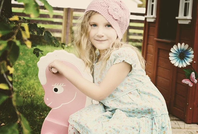 kleines Mädchen mit rosa Strickmütze auf dem Spielplatz
