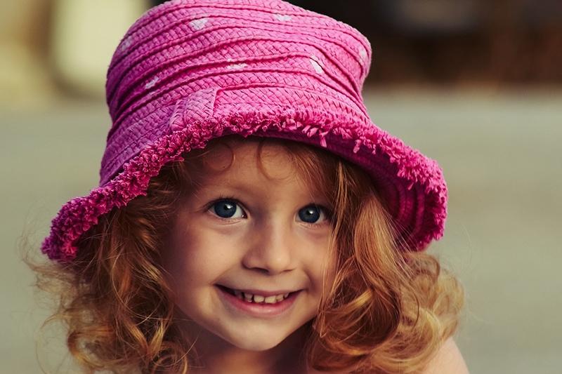 kleines Mädchen mit roten Haaren, das rosa Hut trägt
