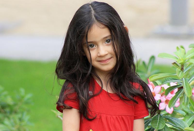 kleines Mädchen mit schwarzen Haaren, das in der Nähe der Blumen im Garten steht