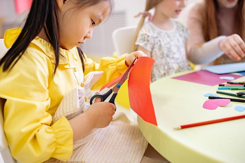 kleines Mädchen schneidet Papier mit einer Schere am Tisch