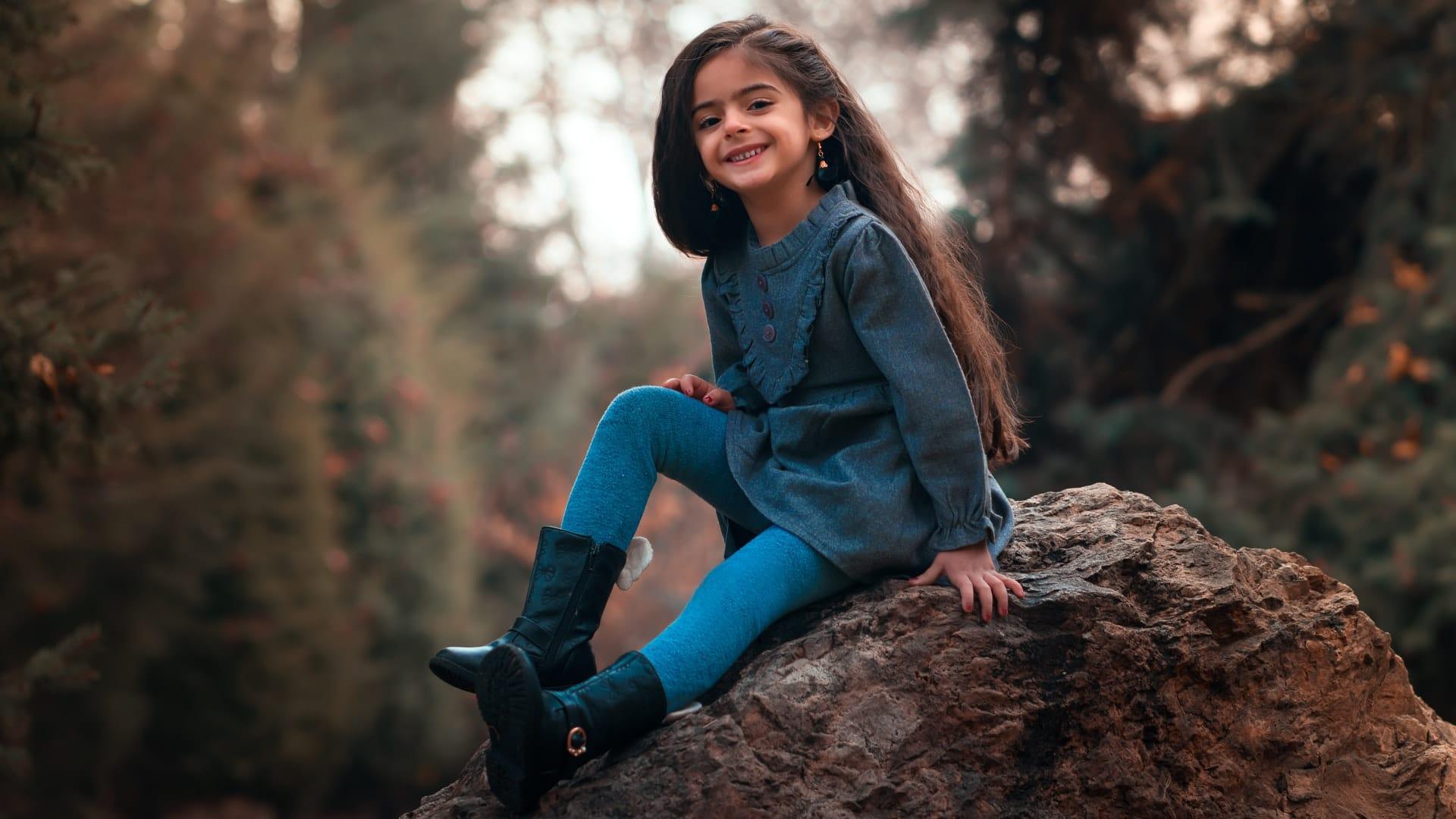 kleines Mädchen sitzt auf dem Felsen im Wald