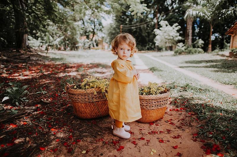 kleines Mädchen steht unter dem Baum in der Nähe von Körben voller Blumen