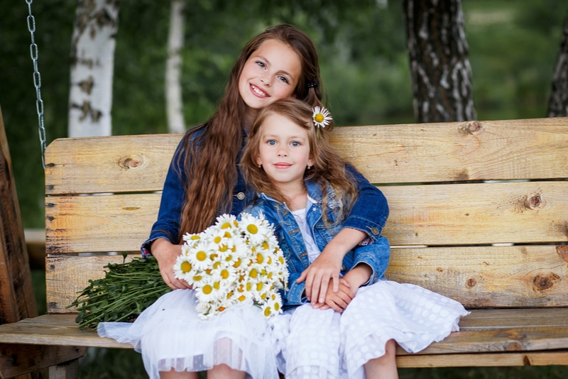 lächelnde Schwestern, die draußen Spaß haben