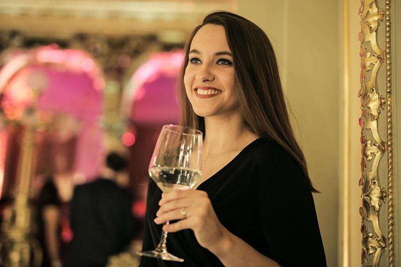 lächelnde Frau mit einem Glas Wein auf der Party